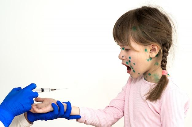 Doktor robi zastrzyk szczepienia dla przestraszonej dziewczynki chorej na ospę wietrzną, wirus odry lub różyczki. szczepienia dzieci w szkole koncepcji.