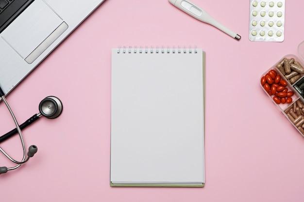 Doktor różowy stół biurkowy ze stetoskopem, medycyna, notatnik. widok z góry z miejsca kopiowania, leżał płasko.