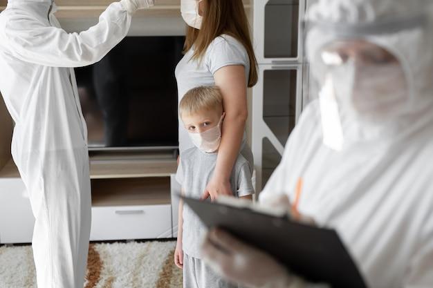 Doktor sprawdź temperaturę ciała pacjenta za pomocą pistoletu na podczerwień termometru na czole w domu. koronawirus, covid-19, kwarantanna, wysoka temperatura.