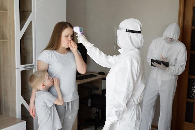 Doktor sprawdź temperaturę ciała pacjenta za pomocą pistoletu na podczerwień termometru na czole w domu. koronawirus, kowid-19, wysoka gorączka i kaszel
