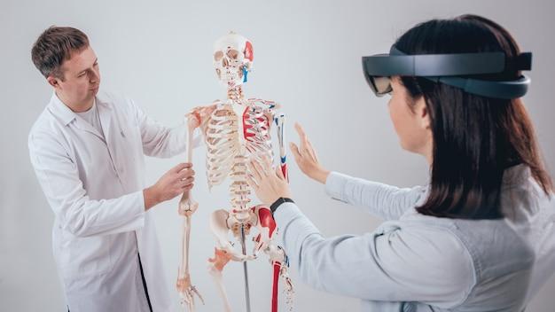 Doktor używa gogli rzeczywistości rozszerzonej i szkieletu ludzkiego do nauczania ucznia
