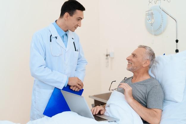 Doktor zabierający do pacjenta w szpitalnym łóżku.