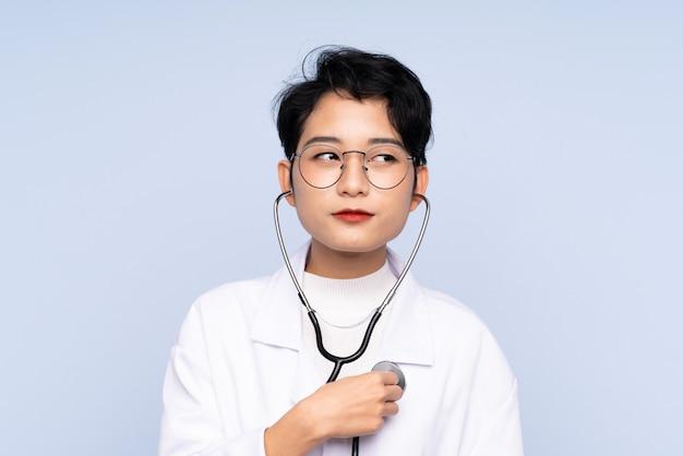 Doktorska azjatycka kobieta z stetoskopem nad odosobnioną błękit ścianą