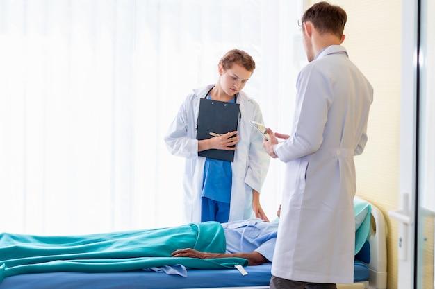 Doktorska caucasian kobieta, mężczyzna rozmowa i sprawdza z pacjentem w sala szpitalnej.