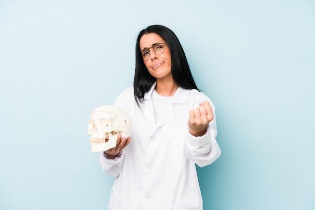Doktorska caucasian kobieta na błękit ścianie pokazuje pięść z agresywnym wyrazem twarzy.
