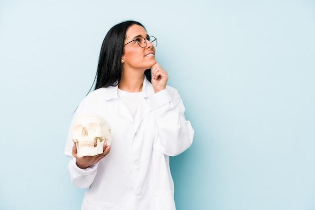 Doktorska caucasian kobieta patrzeje z ukosa na błękit ścianie z wątpliwym i sceptycznym wyrażeniem.