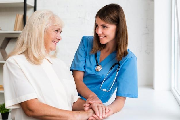 Doktorska i stara kobieta trzyma ręki