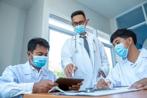 Doktorska jest ubranym maska ochronna chronić przeciw covid-19 spotkaniu w szpitalu, cyfrowego pastylka laptopu mądrze telefon używać, medyczny technologii sieci drużyny spotkania pojęcie.