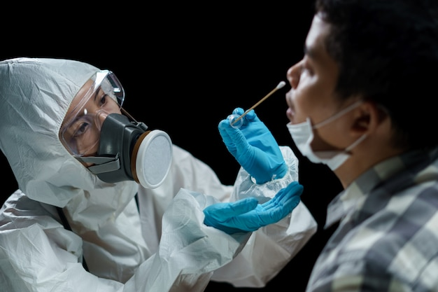 Doktorska kobieta jest ubranym hazmat kostiumy bierze wymaz z nosa w celu przetestowania możliwej infekcji koronawirusem.