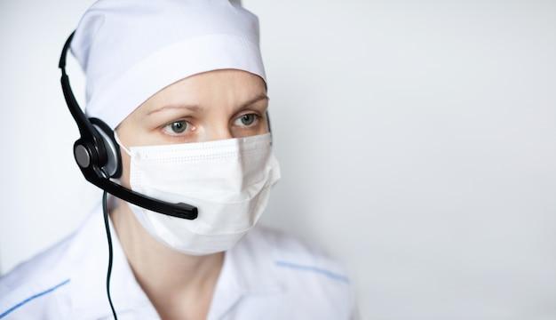Doktorska kobieta jest ubranym ochronną maskę w słuchawki.