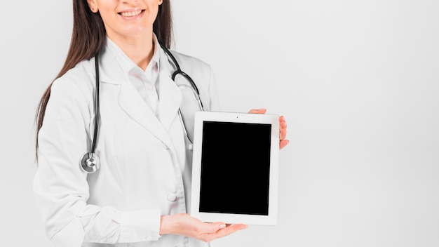 Doktorska kobieta uśmiecha się pastylkę i trzyma