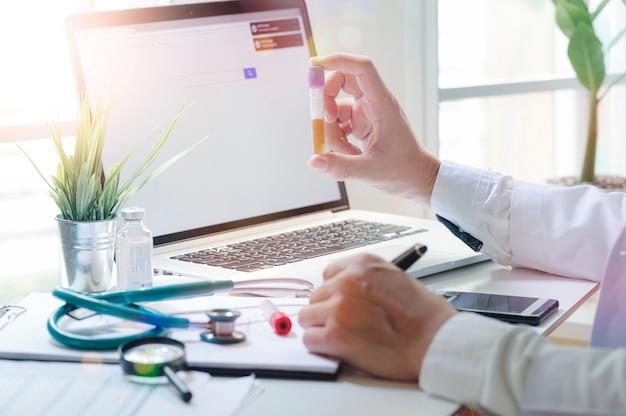 Doktorska mienie moczu tubka dla testa podczas gdy pracujący z laptopem.