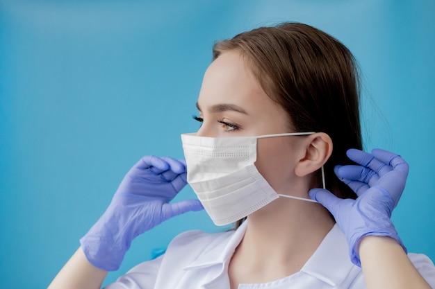 Doktorska pielęgniarka ono uśmiecha się za chirurg maską. zbliżenie portret młody caucasian kobieta model na błękitnym tle. kobieta ubrana w masę, by chronić covid-19