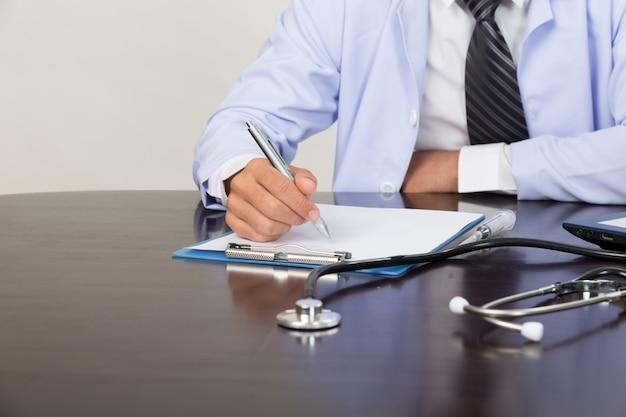 Doktorska pisze rx recepta w medycznym biurze na biurku