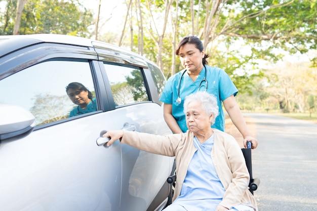 Doktorska pomoc i opieka azjatycka starsza kobieta dostać jej samochód w parku.