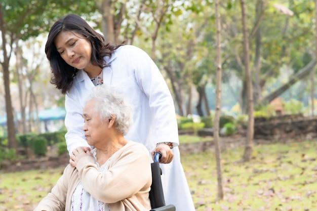 Doktorska pomoc i opieka azjatycki starszy kobiety cierpliwy obsiadanie na wózku inwalidzkim przy parkiem.