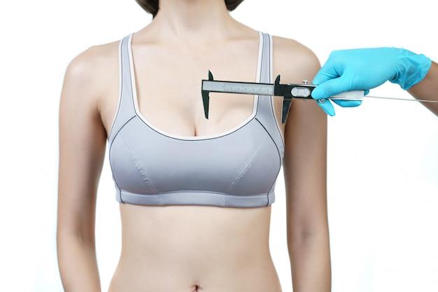 Doktorska ręka pomiaru kobiety pierś z caliper. koncepcja operacji implantu piersi.