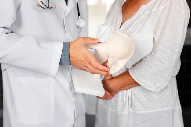 Doktorska ręka trzyma kawałek kość