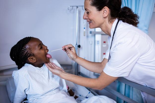 Doktorska sprawdza cierpliwa gorączka od termometru podczas wizyty w oddziale