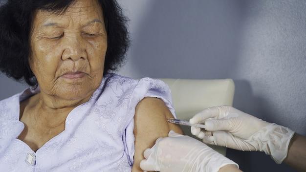 Doktorski daje szczepionki zastrzyk w starszą kobietę