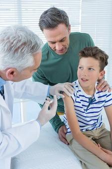Doktorski daje zastrzyk pacjentowi
