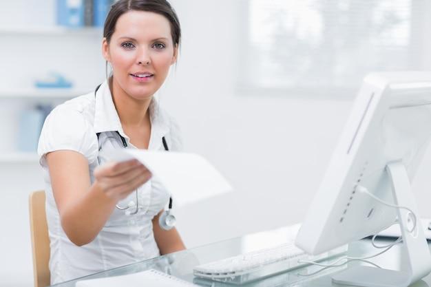 Doktorski dawać ci recepcie przed komputerem przy kliniki biurkiem