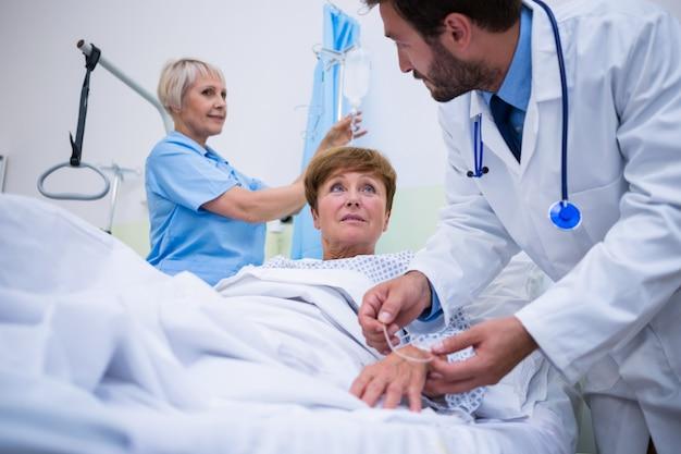 Doktorski dołączający iv kapie na rękę pacjenta