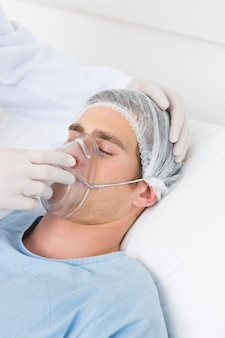 Doktorski dostosowywający maskę tlenową na męskim pacjencie