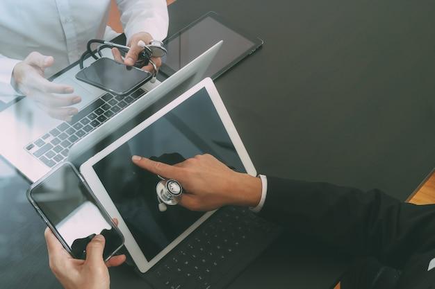Doktorski działanie z mądrze telefonem i cyfrową pastylką i laptopem spotykać jego drużyny w nowożytnym biurze przy szpitalem