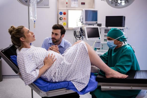 Doktorski egzamininuje kobieta w ciąży podczas dostawy podczas gdy mężczyzna trzyma jej rękę
