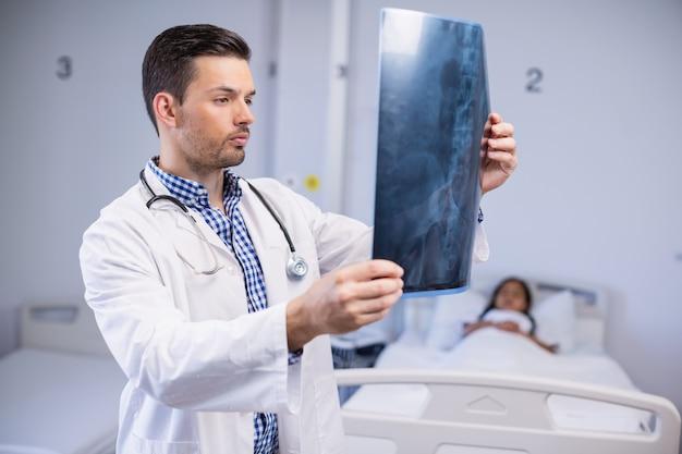 Doktorski egzamininuje promieniowanie rentgenowskie pacjent