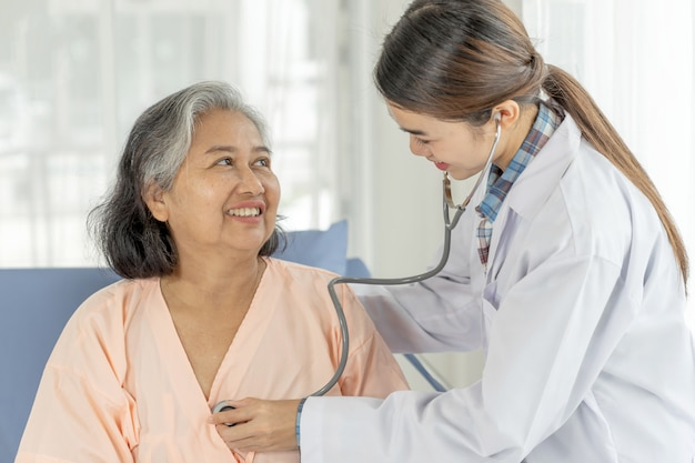 Doktorski egzamininuje starszy starszy żeński pacjent w łóżko szpitalne pacjentach - medyczny i opieka zdrowotna seniora pojęcie