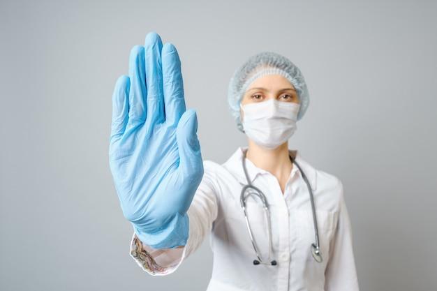 Doktorski jest ubranym medyczną twarzy maskę i jednorazowe rękawiczki pokazuje przerwa gest