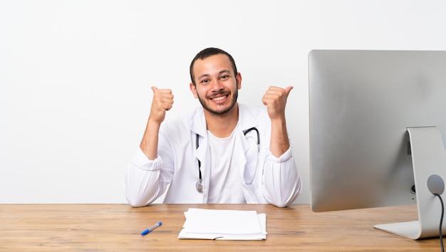 Doktorski kolumbijski mężczyzna z aprobatami gestykuluje i ono uśmiecha się