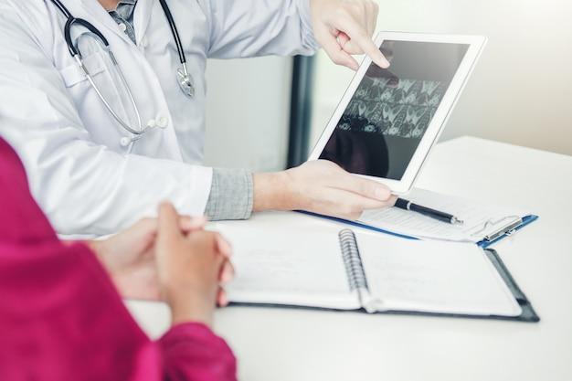 Doktorski konsultować z pacjentem przedstawia promieniowanie rentgenowskie filmu rezultaty na cyfrowym pastylki pastylki obsiadaniu
