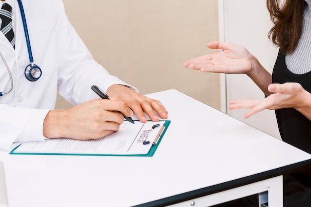 Doktorski medyczny czek w górę informaci z kobieta pacjentem na lekarka stole w szpitalu