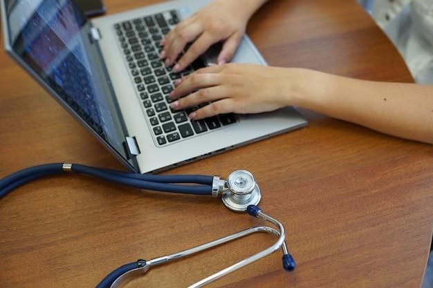 Doktorski pisać na maszynie na komputerze przy biurem