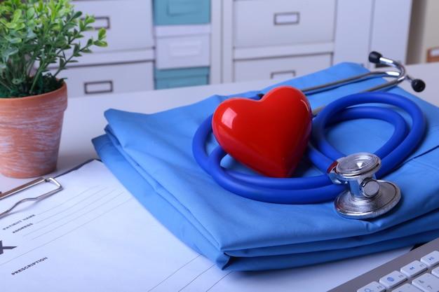 Doktorski płaszcz z medycznym stetoskopem i czerwonym sercem na biurku