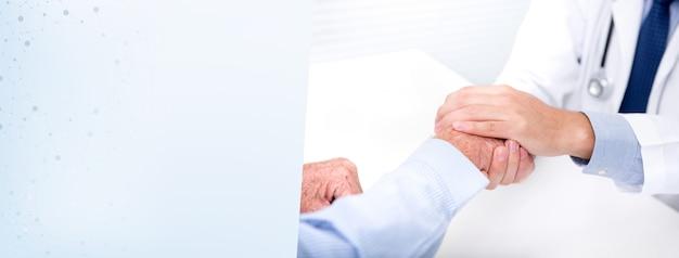 Doktorski pocieszający pacjenta trzymać jego rękę w szpitalu - sztandaru tło