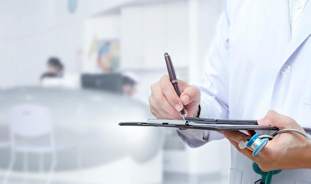 Doktorski ręki writing na podaniowej formie podczas gdy stojący przy szpitalem.