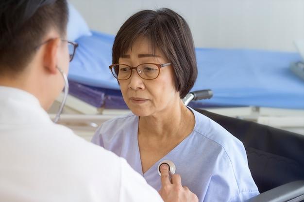 Doktorski sprawdza pacjenta serce z stetoskopem przy szpitalem