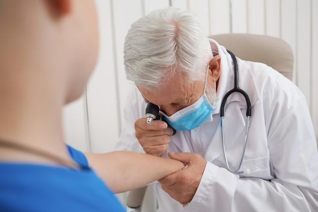 Doktorski używa narzędzie dla badać rękę pacjent.