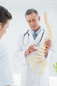 Doktorski wyjaśniający kręgosłup pacjent w biurze