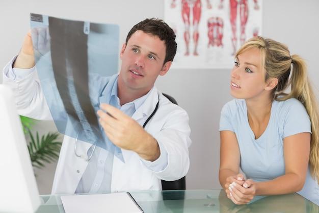 Doktorski zawartość pokazuje pacjentowi coś na xray