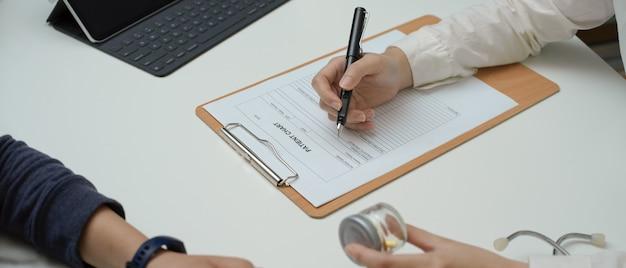 Doktorskie daje pigułki pacjent podczas gdy patrzejący informację na książeczce zdrowia