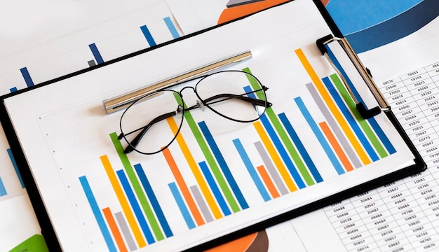 Dokument biznesowy wykres finansowy i wykres z piórem i okularami