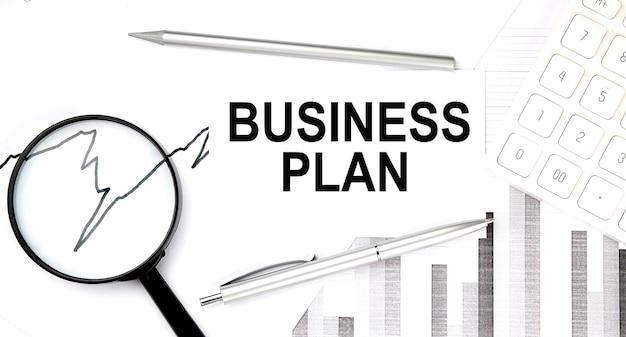 Dokument biznesplanu z piórem, wykresem i lupą, kalkulatorem