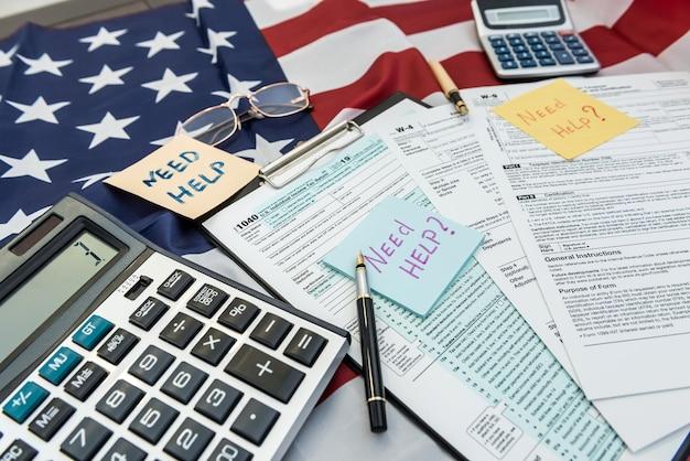 Dokument finansowy 1040, formularz podatkowy z piórem i kalkulatorem na fladze usa. ostateczny termin