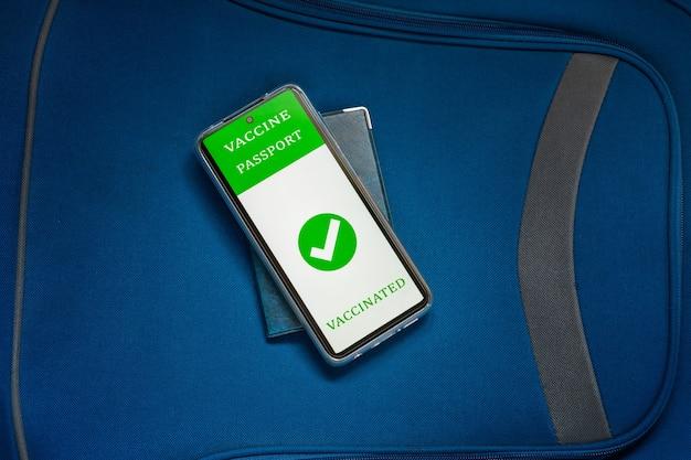 Dokument tożsamości, podręczna torebka bagażowa i cyfrowy paszport szczepionkowy w telefonie komórkowym. nowa normalna koncepcja podróży