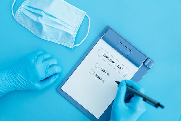 Dokument wyniku testu na wirus korony na niebiesko z niebieskimi rękawiczkami i maską lekarza